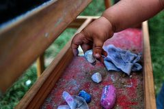 Main de deux années de fille choisissant la craie bleue de diverses craies Photos libres de droits