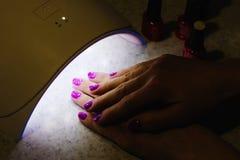 Main de deux femmes à l'intérieur de lampe pour des clous sur la fin de table  Lampe UV Image libre de droits