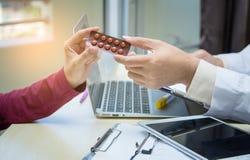 Main de docteur de médecine donnant ou montrant des médicaments au patient images libres de droits