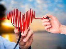 Main de docteur de portrait de plan rapproché écoutant le battement de coeur au coeur SH Images stock