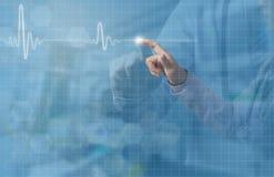 Main de docteur et index touchant sur l'écran de la vague d'ECG photographie stock