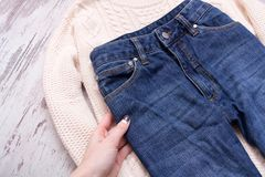 Main de Femaile, chandail blanc et jeans sur un fond en bois Concept à la mode, vue supérieure Photos stock