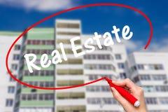 Main de femme écrivant Real Estate avec le marqueur rouge Photographie stock
