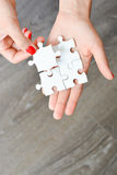 Main de femme adaptant le bon morceau de puzzle suggérant le concept de mise en réseau d'affaires Photo stock