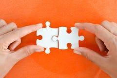 Main de femme adaptant le bon morceau de puzzle suggérant le concept de mise en réseau d'affaires Images libres de droits