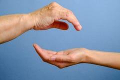 Main de femme agée au-dessus de la main de la jeune femme Photo stock