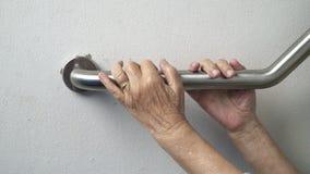 Main de femme agée tenant dessus la balustrade pour l'appui banque de vidéos
