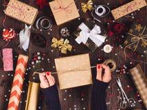 Main de femme attachant l'arc avec la ficelle pour le boîte-cadeau de empaquetage de Noël Image libre de droits