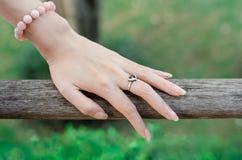 Main de femme avec l'anneau en forme de coeur de l'argent sur le pont en bois Image stock