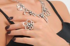 Main de femme avec la bague et le collier sur le cou Photographie stock libre de droits