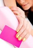 Main de femme avec la carte de visite professionnelle de visite pour le salon de beauté Photographie stock libre de droits