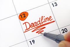Main de femme avec la date-butoir de rappel d'écriture de stylo dans le calendrier image stock