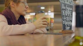 Main de femme avec la tasse de café de papier utilisant le smartphone banque de vidéos