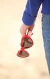 Main de femme avec le coeur formé par lunettes de soleil Images stock