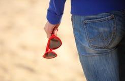 Main de femme avec le coeur formé par lunettes de soleil Image stock