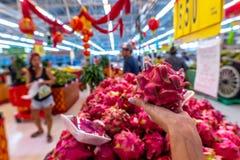 Main de femme avec le fruit du dragon exotique sur un marché local d'aliment biologique photos libres de droits