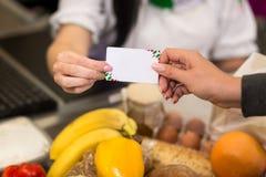 Main de femme avec le grand coup de carte de crédit par le terminal à vendre, dedans images libres de droits
