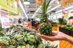 Main de femme avec le petit ananas sur un marché local d'aliment biologique photos stock