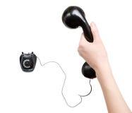 Main de femme avec le rétro téléphone noir Image stock