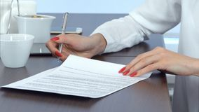 Main de femme avec les clous rouges signant le contrat photo stock