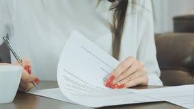 Main de femme avec les clous rouges signant les papiers formels images libres de droits