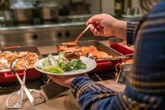 Main de femme choisissant le bifteck de boeuf dans le buffet photographie stock libre de droits