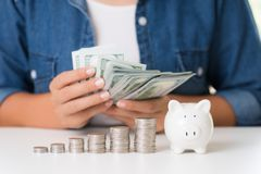 Main de femme comptant l'argent de billets de banque des dollars de l'Amérique avec la pile des pièces de monnaie et de la tireli photographie stock