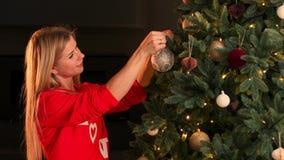 Main de femme décorant l'arbre de Noël avec des lumières de lueur de Noël clips vidéos
