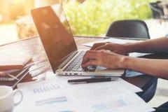 Main de femme d'affaires dactylographiant sur le clavier d'ordinateur portable avec le cha financier images stock