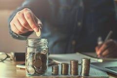 main de femme d'affaires tenant des pièces de monnaie mettant en verre concept finan images stock