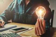 main de femme d'affaires tenant l'ampoule dans le bureau économie de conept photos libres de droits