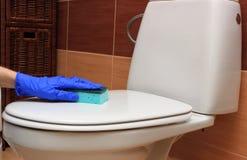 Main de femme dans la cuvette des toilettes bleue de nettoyage de gant Image libre de droits