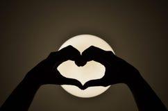 Main de femme de forme de coeur faisant sur la lumière Photos libres de droits
