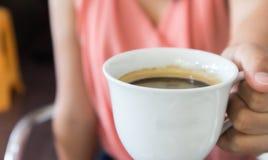 Main de femme de plan rapproché tenant une tasse de café chaud d'americano, choisie Photographie stock libre de droits