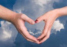 Main de femme et d'homme montrant la forme de coeur Photo stock