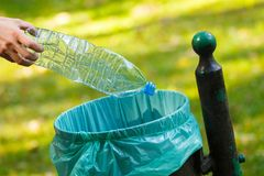 Main de femme jetant la bouteille en plastique dans le bac de recyclage Photographie stock