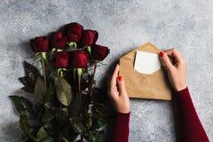 Main de femme de jour de valentines tenant la lettre d'amour d'enveloppe avec le jour de mères de carte de voeux Photo libre de droits