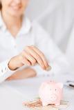 Main de femme mettant la pièce de monnaie dans la petite tirelire Photos stock