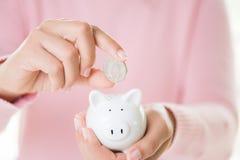 Main de femme mettant la pièce de monnaie dans la tirelire Richesse d'argent d'économie et financier photos libres de droits