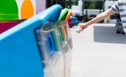 Main de femme mettant le papier utilisé dans la poubelle réutilisée à l'aire de stationnement Photographie stock libre de droits
