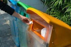 Main de femme mettant le papier utilisé dans la poubelle réutilisée à l'aire de stationnement d photos libres de droits