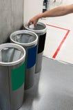 Main de femme mettant le papier utilisé dans la poubelle réutilisée Couleur différente t Images stock