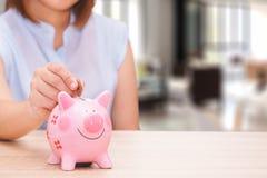 Main de femme mettant une pièce de monnaie dans une tirelire rose sur le bureau en bois Photographie stock libre de droits