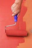 Main de femme peignant un plancher sur le rouge de couleur Photographie stock libre de droits