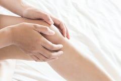 Main de femme de plan rapproché tenant le genou avec douleur sur le lit, soins de santé photos stock