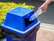Main de femme de portrait de plan rapproché jetant la bouteille d'eau en plastique vide Images libres de droits