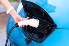 Main de femme poussant le câble dans la voiture Photos libres de droits