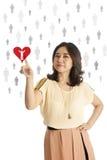 Main de femme poussant sur un retrait rouge de coeur Images stock