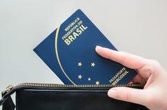 Main de femme prenant le passeport brésilien hors du sac photographie stock