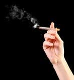 Main de femme retenant une cigarette images stock